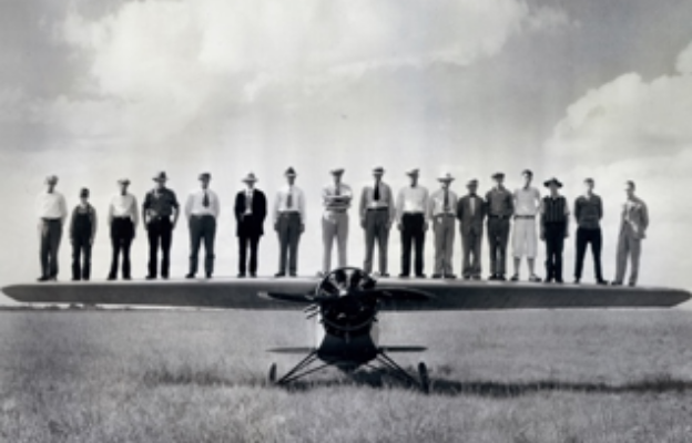 historic photo of men standing on propeller aircraft in Wichita Kansas, Air Capital of the World