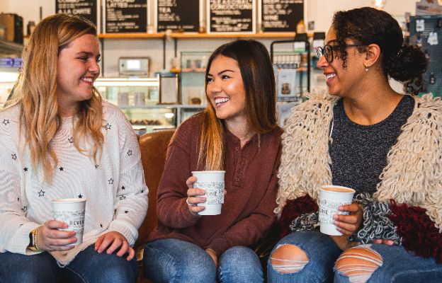 three girls enjoying coffee at reverie roasters in downtown wichita, kansas talking about the holiday gift guide