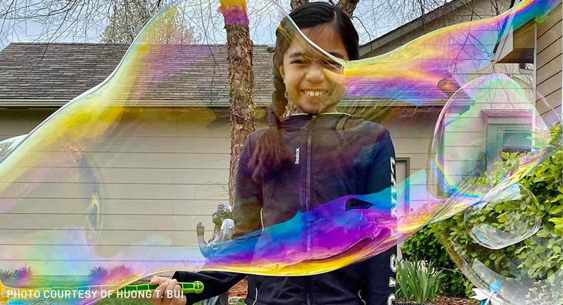 girl playing with bubble wand in wichita, kansas